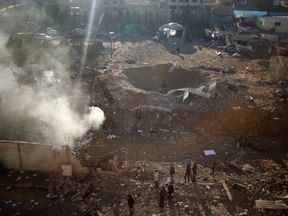 Palestinians look at a militant target that was hit in an Israeli airstrike in the northern Gaza Strip