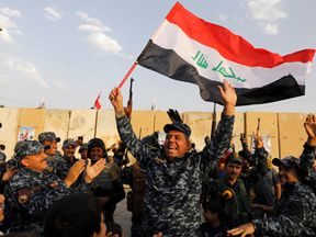 A member of Iraqi Federal Police waves an Iraqi flag as they celebrate victory of military operations against the Islamic State militants in West Mosul, Iraq July 2,