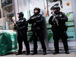 Armed police stand in Times Square following the botched bomb attack
