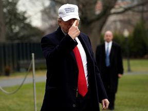 U.S. President Donald Trump points to his hat for the press on South Lawn as he returns to the White House