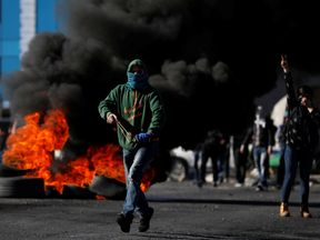 A Palestinian protester runs during clashes with Israeli troops