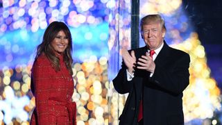US President Donald Trump (R) gestures as First Lady Melania Trump smiles during the 95th annual National Christmas Tree Lighting ceremony at the Ellipse in President's Park near the White House in Washington, DC on November 30, 2017