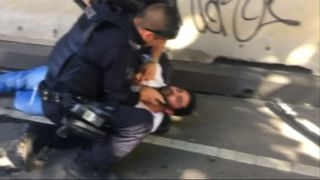Police try to rouse the arrested man, who appears to be unconscious