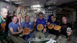 The astronauts with their pizzas in space