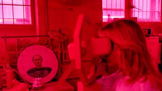 """A woman looks at an installation which includes a painting depicting Russian president Vladimir Putin at the """"SUPERPUTIN"""" exhibition"""