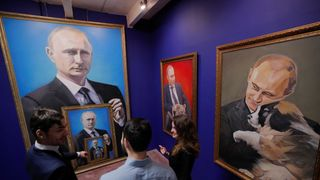 """People look at the paintings depicting Russian president Vladimir Putin at the """"SUPERPUTIN"""" exhibition in UMAM museum in Moscow, Russia"""