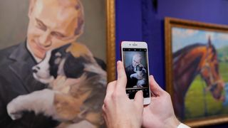 """A man takes a picture of a painting depicting Russian president Vladimir Putin at the """"SUPERPUTIN"""" exhibition"""