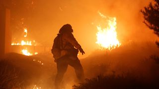 A firefighter stomps out small embers on a ranch