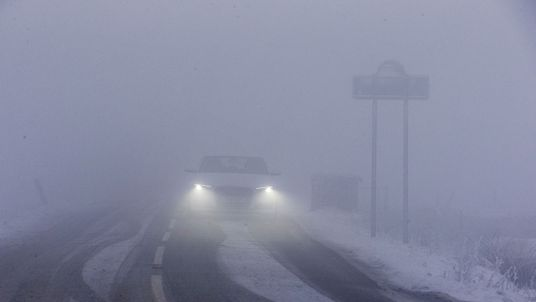 A car drives slowly through the fog and snow on one of the rural roads in Derbyshire, northern England on December 10, 2017. The heaviest snowfall to hit Britain in four years caused widespread disruption on Sunday, with roads becoming hazardous and flights grounded following runway closures. / AFP PHOTO / Lindsey Parnaby (Photo credit should read LINDSEY PARNABY/AFP/Getty Images)