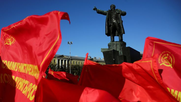 Flags flutter in front of a monument to Soviet state founder Vladimir Lenin during a rally held by Russian Communist Party supporters in St. Petersburg