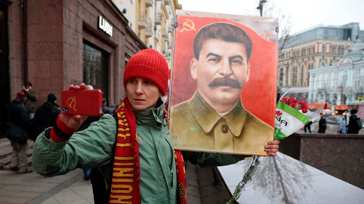 A demonstrator takes a selfie with a portrait of Soviet dictator Josef Stalin in central Moscow