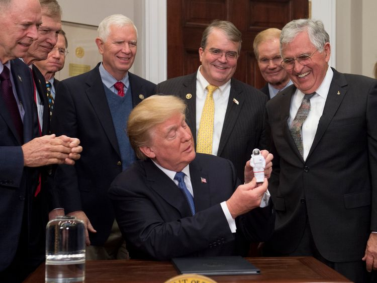 US President Donald Trump holds up an astronaut toy alongside former US Senator and Apollo 17 Astronaut Jack Schmitt