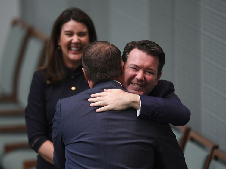 MP Tim Wilson is congratulated by Senator Dean Smith after Wilson proposed to his partner Ryan Bolger during debate of the Marriage Amendment bill in Australia's House of Representatives