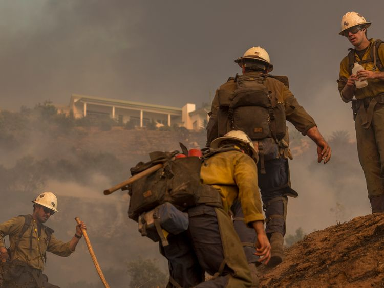 A Hot Shot crew climbs a hill while cutting a line among homes at the Thomas Fire on December 16, 2017 in Montecito, California. The National Weather Service has issued red flag warnings of dangerous fire weather in Southern California for the duration of the weekend. Prior to the weekend, Los Angeles and Ventura counties had 12 consecutive days of red flag fire warnings, the longest sustained period of fire weather warnings on record. The Thomas Fire is currently the fourth largest California