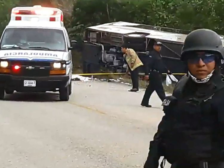 Video grab of Mexican police officers standing guard in the area where a bus driving tourists to Chacchoben archaeological zone overturned in the road between El Cafetal and Mahahual, in Quintana Roo state, Mexico on December 19, 2017. At least eleven tourists who arrived in the Mexican Caribbean on a US cruise ship were killed and another 20 injured in a road accident on Tuesday when they were heading to an archaeological zone, the Quintana Roo state government reported. / AFP PHOTO / Manuel Je