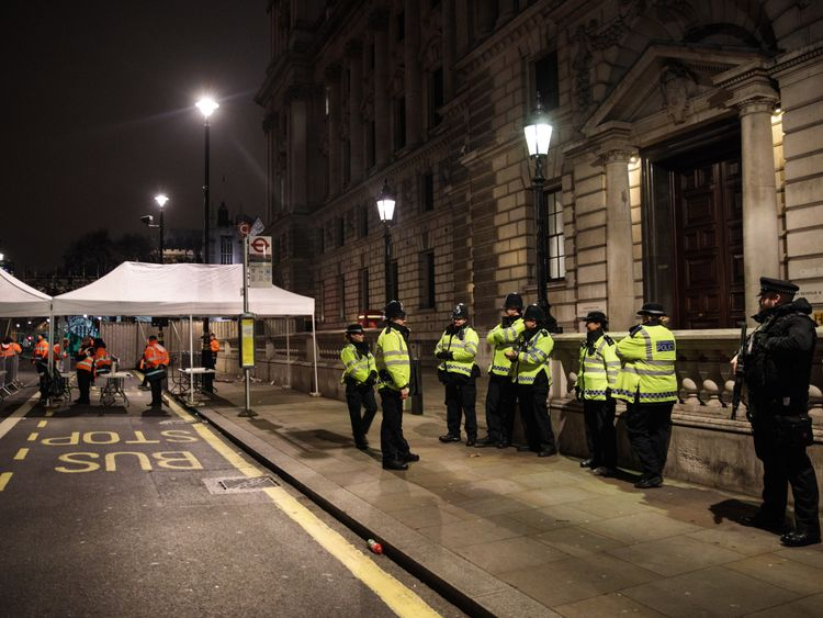 LONDON, ENGLAND - DECEMBER 31: Police and armed police officers standby next to a security checkpoint on Whitehall ahead of the New Year's Eve fireworks display on December 31, 2016 in London, England. Security has been stepped-up in London following the Berlin and Nice lorry attacks as thousands of people line the banks of the River of Thames tonight to watch the annual New Year's Eve fireworks display. (Photo by Jack Taylor/Getty Images)