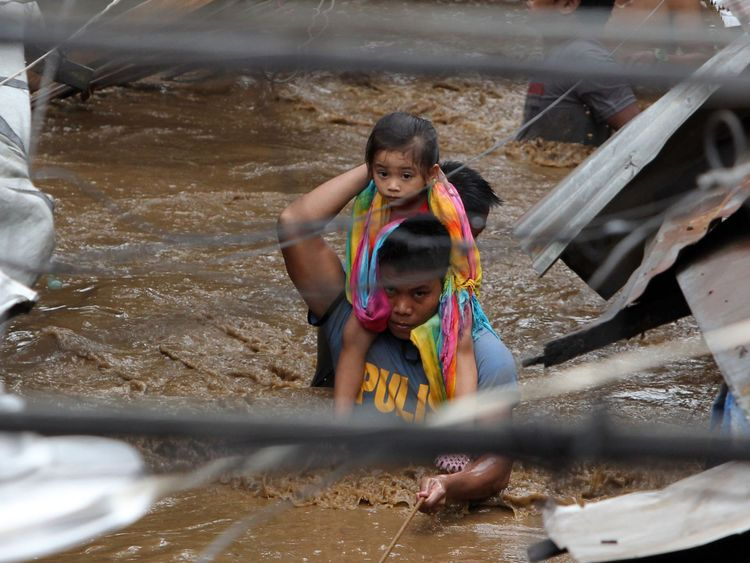 A policeman carries a young girl along a flooded street in Cagayan City