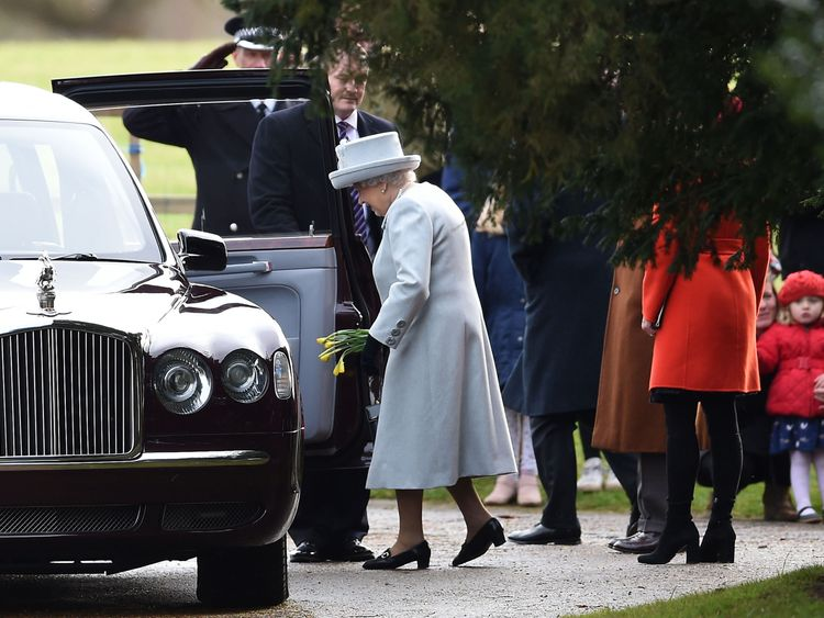 The Queen carries daffodils given by a girl (right) after attending the morning church service at St Mary Magdalene Church in Sandringham, Norfolk
