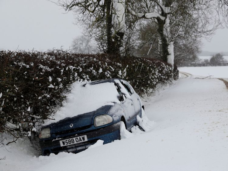 A stranded car lies in a ditch after snow fall in Stanford on Avon