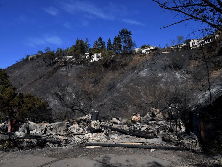 burnt out house is seen after the Skirball wildfire swept through the exclusive enclave of Bel Air, California on December 7, 2017. Local emergency officials warned of powerful winds on December 7 that will feed wildfires raging in Los Angeles, threatening multi-million dollar mansions with blazes that have already forced more than 200,000 people to flee. / AFP PHOTO / MARK RALSTON (Photo credit should read MARK RALSTON/AFP/Getty Images)