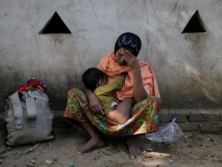 A Rohingya refugee woman breast-feeds her child after they crossed Myanmar-Bangladesh border at the village of Maughpara near Cox's Bazar, Bangladesh