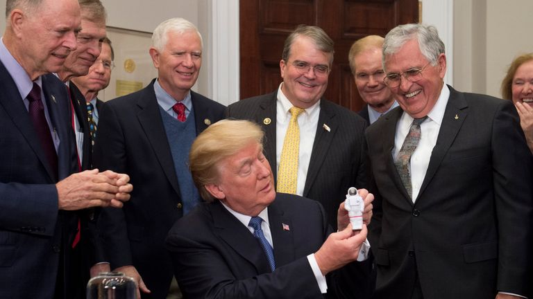 US President Donald Trump holds up an astronaut toy alongside former US Senator and Apollo 17 Astronaut Jack Schmitt