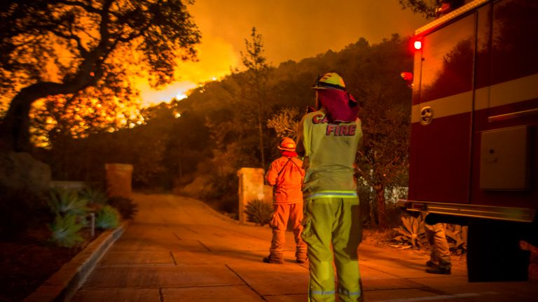 MONTECITO, CA - DECEMBER 12:  Firefighters watch flames as the Thomas Fire approaches homes on December 12, 2017 in Montecito, California. The Thomas Fire has spread across 365 miles so far and destroyed about 800 structures since it began on December 5 in Ojai, California.  (Photo by David McNew/Getty Images)