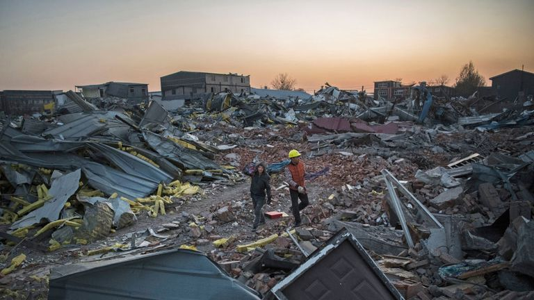 Chinese workers salvage items from buildings demolished by authorities in an area that used to have migrant housing