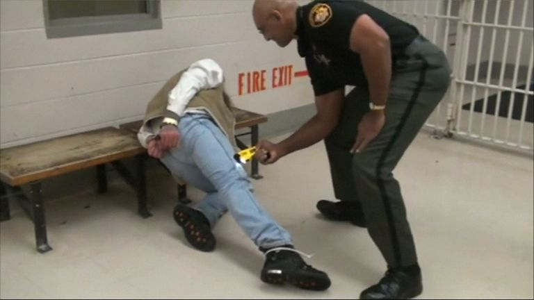 A guard at Franklin County Jail in Ohio presses a Taser gun into the leg of inmate in December 2009.