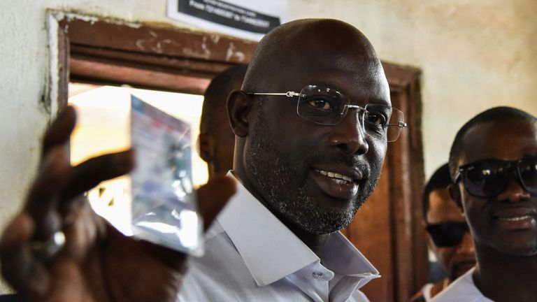 Former international Liberian football star turned politician, and presidential election candidate George Weah shows his voting card prior to casting his vote for Liberia's presidential and legislatives elections, at a polling station in Monrovia on October 10, 2017. Liberians head to the polls on October 10 to elect a new president in a contest set to complete the country's first democratic transition of power in more than 70 years. / AFP PHOTO / ISSOUF SANOGO (Photo credit should read ISSOUF S
