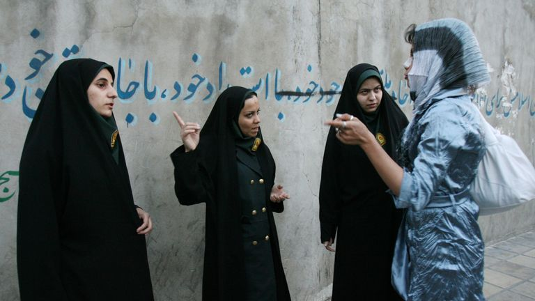 Iranian policewomen warn a woman about her clothing and hair during a crackdown to enforce Islamic dress code on April 22, 2007 in Tehran, Iran.