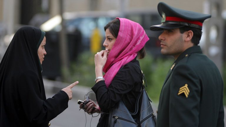 An Iranian policewoman (L) warns a woman about her clothing and hair during a crackdown to enforce Islamic dress code on April 22, 2007 in Tehran, Iran