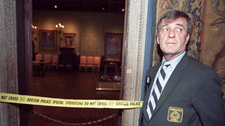 """Security guard Paul Daley stands guard at the door of the Dutch Room of the Isabella Stewart Gardner Museum in Boston March 21, 1990. Twelve priceless works of art were stolen from the museum March 18, including Rembrandt's """"The Storm on the Sea of Galilee,"""" which hung in the empty wall space seen in the right background. Reuters/Jim Bourg BEST QUALITY AVAILABLE"""