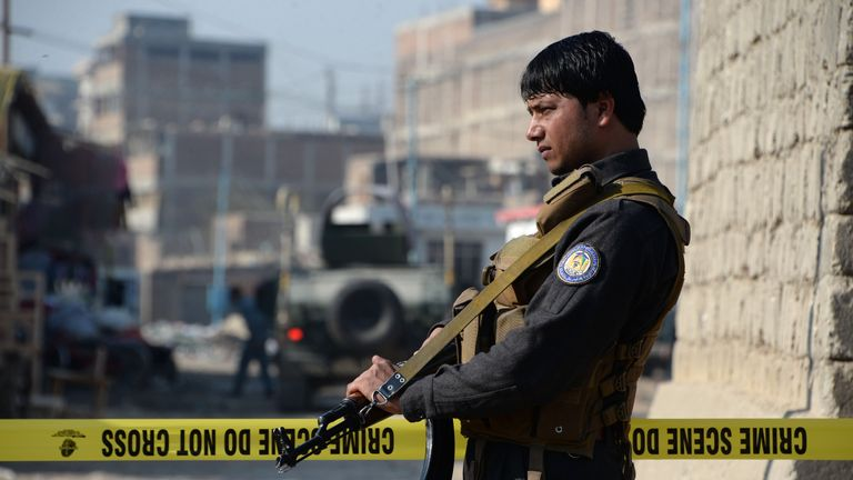 An Afghan security force guard stands at the site of blast near a TV station in Jalalabad