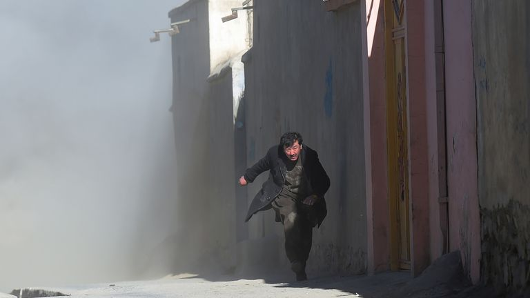 An Afghan man runs away as dust blows in the aftermath of the third blast at a Shiite cultural centre in Kabul on December 28, 2017. At least 40 people were killed and dozens more wounded in multiple blasts at a Shiite cultural centre in Kabul on December 28, officials said, in the latest deadly violence to hit the Afghan capital. / AFP PHOTO / SHAH MARAI (Photo credit should read SHAH MARAI/AFP/Getty Images)