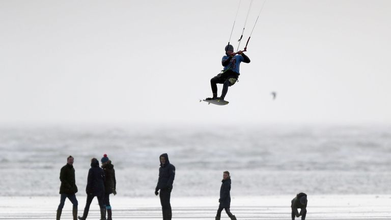 A kite surfer enjoys the strong winds on West Wittering beach in West Sussex