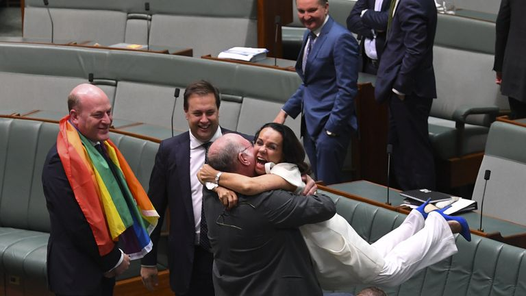 Liberal MP Warren Entsch lifts up Labor MP Linda Burney as they celebrate the passing of the Marriage Amendment Bill