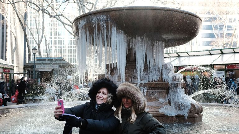 Women take a selfie in front of a frozen fountain in Bryant Park, Manhattan