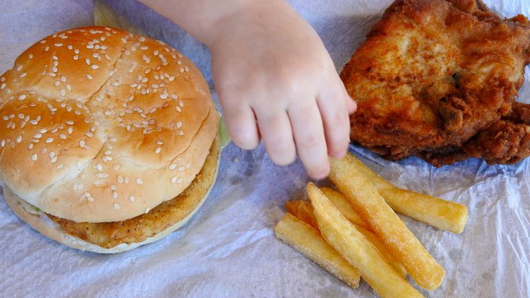 A young girls eats a chicken burger, French fries and fried chicken.