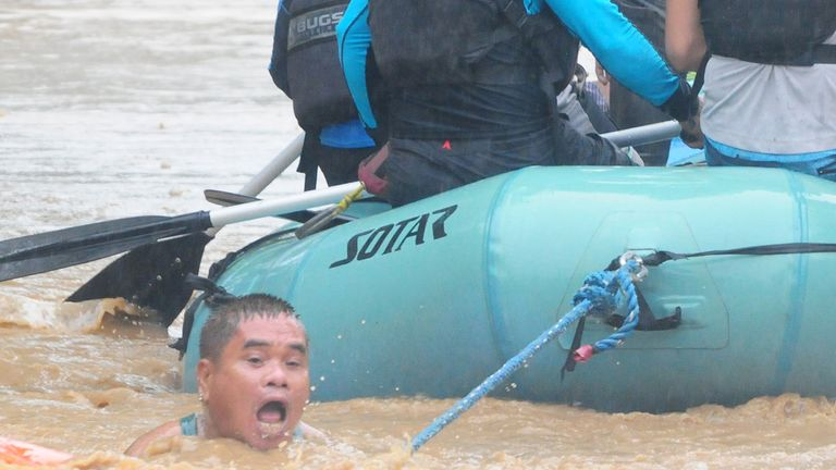A man clings onto the rope of a rescue in the city of Cagayan de Oro
