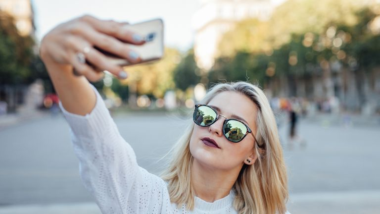 Young woman takes a selfie with a mobile phone
