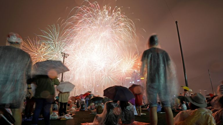 People watch fireworks in the rain ahead of the New Year at Marina Bay in Singapore