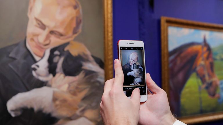 "A man takes a picture of a painting depicting Russian president Vladimir Putin at the ""SUPERPUTIN"" exhibition"