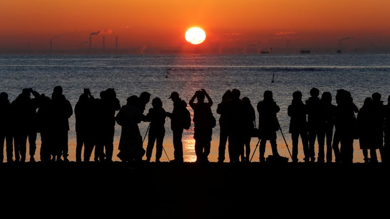 People watch the first sunrise on New Year's Day at a beach in Tokyo, Japan, January 1, 2018