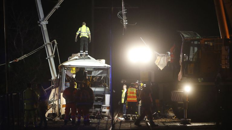 Firefighters and police at the site of an accident near Perpignan in southern France, where a train crashed into a school bus at a level crossing