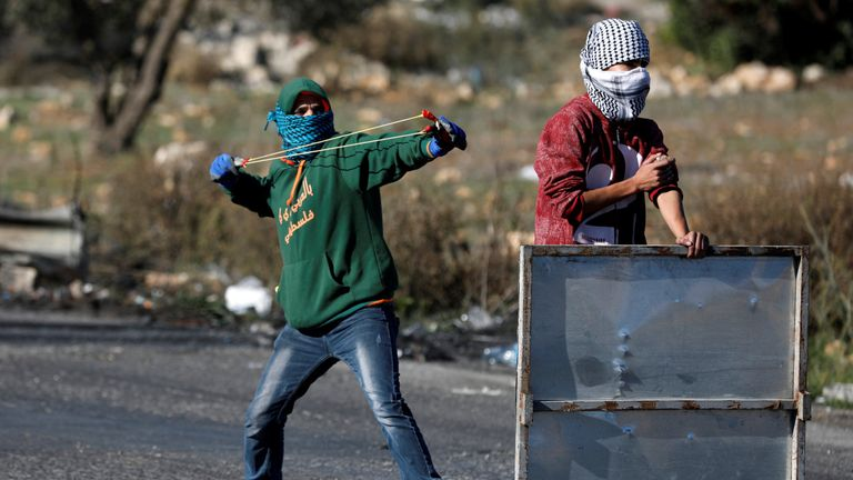A Palestinian protester uses a sling shot to hurl stones towards Israeli troops during clashes in Ramallah