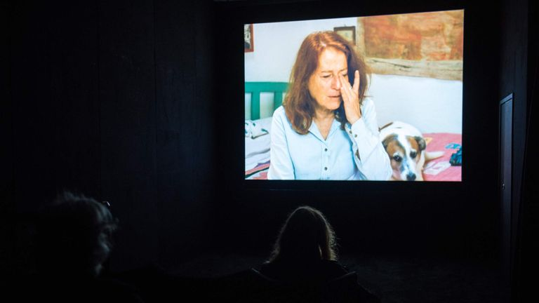 A video piece by Nashashibi being watched by the public