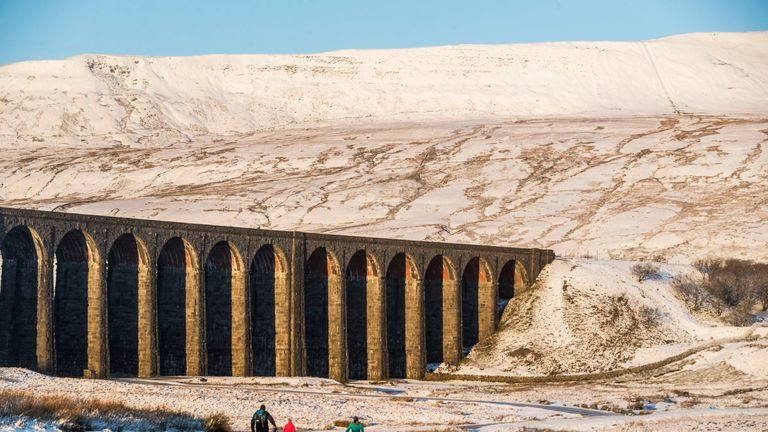 Walkers at Ribblehead Viaduct in Yorkshire, as parts of Britain woke up to a blanket of snow caused by an Arctic airflow in the wake of Storm Caroline