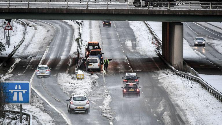 A man warns motorists to pass slowly following an incident on the A417 between Gloucester and Cheltenham