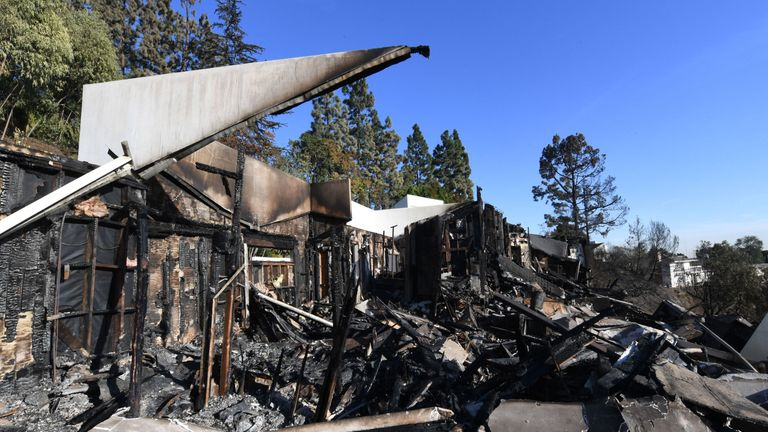 A burnt out home is seen after the Skirball wildfire swept through the exclusive enclave of Bel Air, California on December 7, 2017. Local emergency officials warned of powerful winds on December 7 that will feed wildfires raging in Los Angeles, threatening multi-million dollar mansions with blazes that have already forced more than 200,000 people to flee. / AFP PHOTO / MARK RALSTON (Photo credit should read MARK RALSTON/AFP/Getty Images)